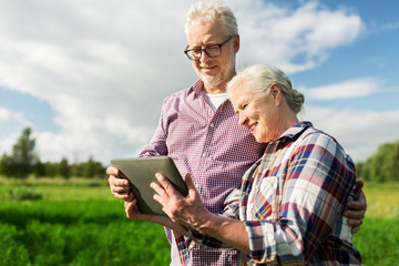 Fotobehang Vissen happy senior couple with tablet pc at summer farm