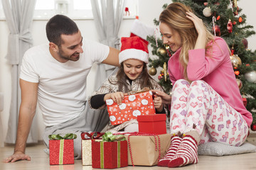 Young family sitting in front of Christmas tree opening presents