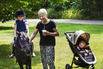 Woman, baby in pushchair and blond girl wearing riding hat sitting on a pony.