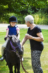 Woman and blond girl wearing riding hat sitting on a pony.