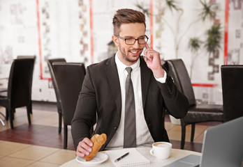 Young businessman working in cafe while having snack