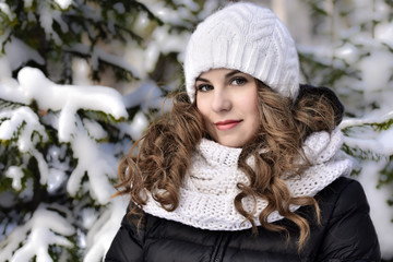 Girl in a white knitted hat for a walk in the winter forest