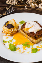 Dish with meat steak on toast, potato chips  melted cheese and poached egg  Dutch sauce. Wooden background. Top view. Close-up
