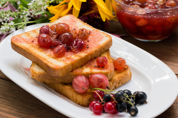 Toast with gooseberry jam. Wooden background  flowers. Top view. Close-up