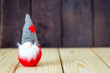 Little Cute Christmas Gnome on The Wooden Background with Free Space for Your Text