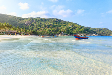Phangan beach with white sand and traditional long tail boats on cristal clear water