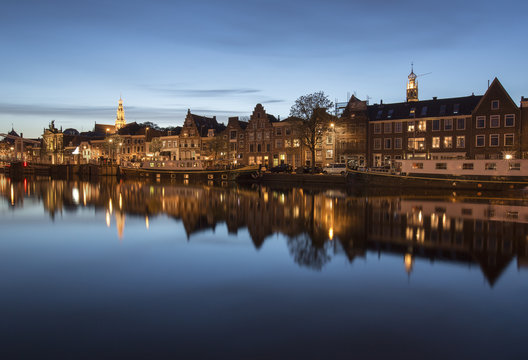 Twilight at port area of Haarlem, Holland , with houses reflected in the Spaarne canal, Haarlem, North Holland, Netherlands