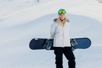 Young woman and her snowboard on snow-covered mountainside at sunset