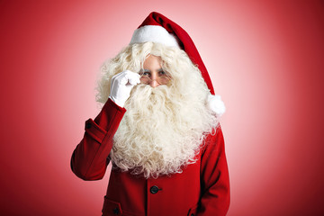 Santa Claus with a kind smile and a large white beard in red coat and hat and white gloves adjusting his glasses on red background