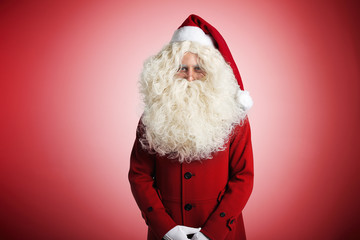 Smiling Santa Claus in a pretty woolen red coat and gold rim glasses on red background