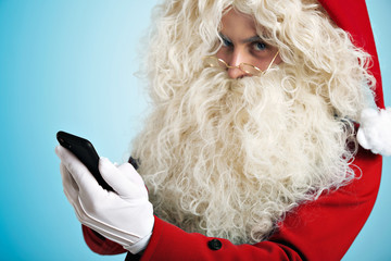 Unfocused Santa looking at camera abore his golden round glasses and holding focused smartphone in his hand on foreground