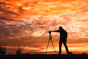Silhouette image of a photographer with a sunset background .
