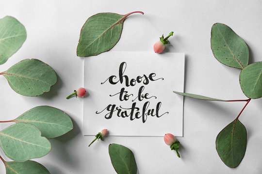 "Quote ""Choose to be grateful"" written on paper with leaves and berries on white background. Top view"