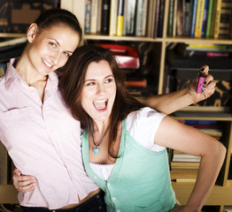 two cute girlfriends taking photo of themselves in library, lifestyle people concept