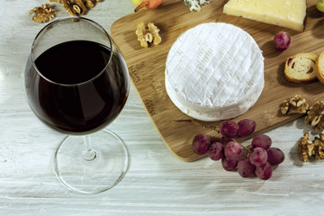 Wine, cheese, grapes and nuts on wooden board