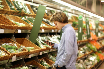 Young man in the supermarket .Young man buying vegetables at the market