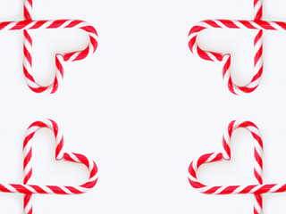 Traditional Christmas candy - candy cane, shepherd's staff, decorated with red and white stripes. Sandy Cane heart shaped background