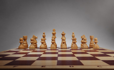 Chessboard with chess pieces. White set, front wide view angle.
