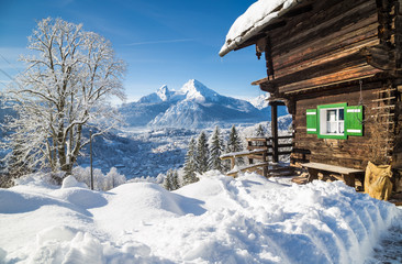 Winter wonderland scenery in the Alps with traditional mountain chalet