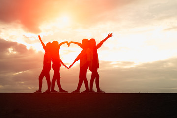 Four female silhouettes hands making a heart shape with sunset b