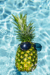 A pineapple swimming in a pool