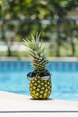 A pineapple relaxing by the pool