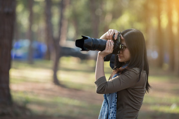 Woman photographer holding a camera in the wild for take a photo