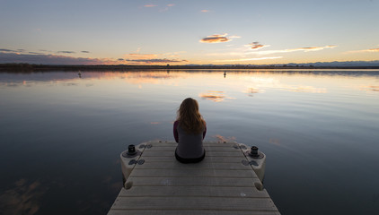 Girl sitting on Dock Sunset