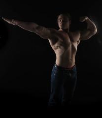 naked torso male bodybuilder athlete in the studio on a black background
