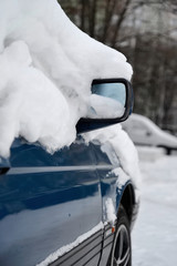Car is covered with snow as it has been left on open air in snowfall.