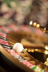 Golden Casino theme. High contrast image of casino roulette, poker game, dice game, poker chips on a gaming table, all on colorful bokeh background. Place for typography and logo.