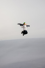 Young woman jumping with her snowboard