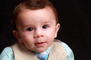 Curious Little Baby Boy Infant In Blue Suit With a Black Background