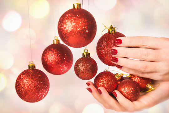 Close up of caucasian female hands with professional red manicure with glittering sparkles isolated on Christmas background. Woman holding New Year round balls ready to decorate tree.