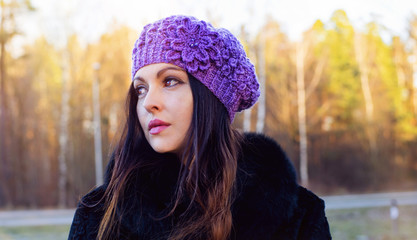 The girl on walk in a knitted cap