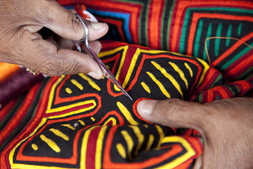 Kuna indigenous woman sewing a mola in the San Blas Islands, Panama, Central America