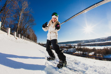 Young woman with the snowboard shooting a selfie by her action camera