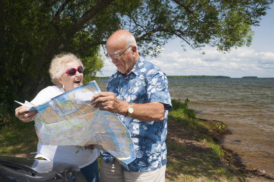 Senior Caucasian couple in their 70s look at a road map beside their car outdoors near Millelac Lake in northern Minnesota