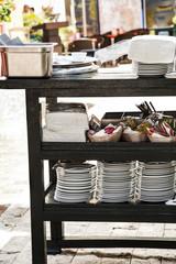 mesa auxiliar en restaurante al aire libre con platos,cubiertos y servilletas