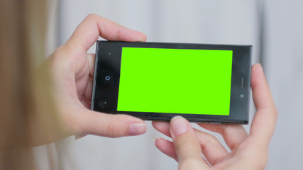Woman looking at horizontal smartphone with green screen. Close up shot of woman's hands with mobile. White wooden background