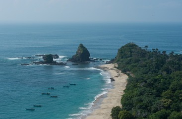 Blue sea with white foam bathes coastal reefs near the shore, nestled in green forest (Indonesia)