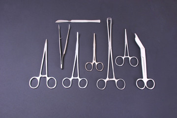 surgical instruments and tools including scalpels, forceps  tweezers arranged on a table for  surgery