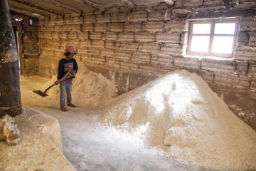 Small girl shoveling salt inside a Salt factory where workers process salt from Salar de Uyuni, Colchani, Bolivia, South America