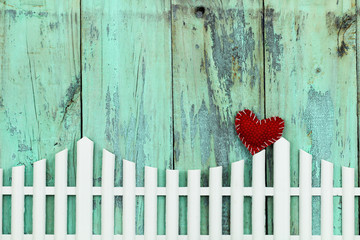 Blank wood sign with white picket fence and red heart