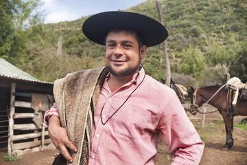 Portrait of a Chilean cowboy (arriero) in a hat on a horse farm in El Toyo region of Cajon del Maipo, Chile, South America