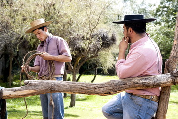 Two Chilean cowboys conversing outside stable on a horse ranch in El Toyo region of Cajon del Maipo, Chile, South America