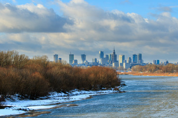 Warsaw sky line with skyscrapers of city center, Vistula river shore in winter