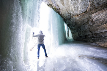 Man stands behind a frozen waterfall and looks out through an opening, Minnehaha Falls in winter, Minneapolis, Minnesota