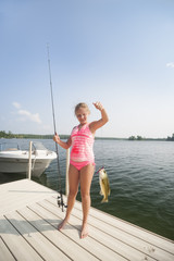 Caucasian young girl 10-13 years wearing a pink swimsuit shows the fish she caught from the dock on Ten Mile Lake, Minnesota, United States of America, North America