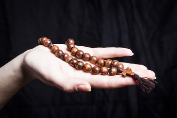Rosary and cross in female hands on a dark background
